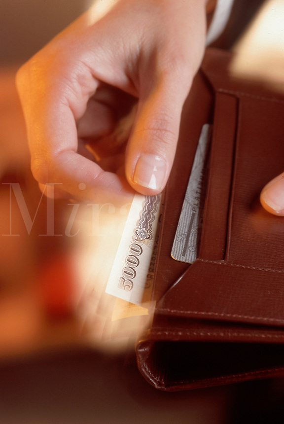 A hand taking japanese yen out of a wallet.