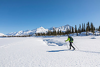 Man on cross country skis in the Alaska Range mountains.