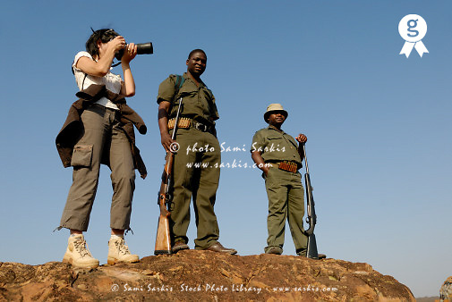 Female tourist taking photo, two park rangers, low angle view, Kruger NP, South Africa (Licence this image exclusively with Getty: http://www.gettyimages.com/detail/200503582-001 )