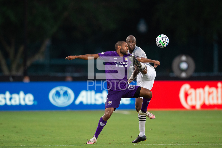 LAKE BUENA VISTA, FL - JULY 25: Tesho Akindele #13 of Orlando City SC and Rod Fanni #7 of the Montreal Impact battle for the ball during a game between Montreal Impact and Orlando City SC at ESPN Wide World of Sports on July 25, 2020 in Lake Buena Vista, Florida.