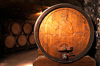 Wooden storage vat with aging wine in the cellar of Guigal in Ampuis. The end of the vat is carved with a portrait of Etienne Guigal, the founder of the Guigal wine company, depicting him taking a sample of wine with a pipette. The vat is still in use for storing wine.  Domaine E Guigal, Ampuis, Cote Rotie, Rhone, France, Europe