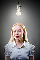 Young blonde woman underneath lit light bulb