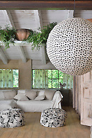 A rustic style living room with a painted beamed ceiling and a wood floor. The room is furnished with a sofa with neutral covers and two black and white patterned pouffes. A paper globe light hangs from the ceiling.