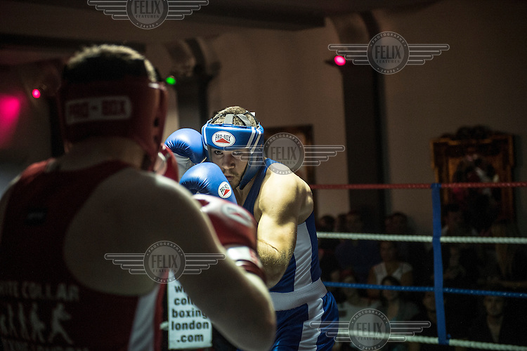 Laurence Mills (right) fights Ross Griffiths at a white collar boxing event at the London Irish Centre where the 'Carpe Diem' boxing event is taking place. <br /> <br /> 'White-collar boxing' is a growing phenomenon amongst well paid office workers and professionals and has seen particular growth in financial centres like London, Hong Kong and Shanghai. It started at a blue-collar gym in Brooklyn in 1988 with a bout between an attorney and an academic and has since spread all over the world. The sport is not regulated by any professional body in the United Kingdom and is therefore potentially dangerous, as was proven by the death of a 32-year-old white-collar boxer at an event in Nottingham in June 2014. The London Irish Centre, amongst other venues, hosts a regular bout called 'Carpe Diem'. At most bouts participants fight to win. Once boxers have completed a few bouts they can participate in 'title fights' where they compete for a replica 'belt'.