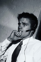 A young executive man with a phone headset and a tense, apprehensive expression.