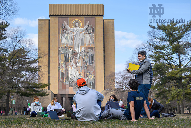 """March 8, 2021; Associate Teaching Professor Marcio Bahia teaches his Romance Languages and Literatures course """"Brazil: Giant of the South"""" on the Library Quad on the first day of 2021 to top 60 degrees. (Photo by Matt Cashore/University of Notre Dame)"""