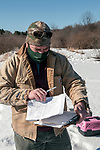 New Hampshire Fish and Game Biological Technician, Brett Ferry refers to data sheets when looking up if he had previously trapped a New England cottontaol rabbit inside the Great Bay National Wildlife Refuge.