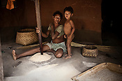 A tribal Chattisgarhi woman is seen crushing paddy in her hut in Nendra village in Chattisgarh, India. Photo: Sanjit Das/Panos for Forbes