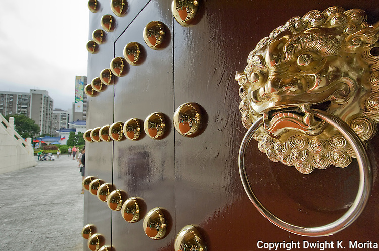 The entrance doors to the National Democracy Memorial Hall, built to honor Chiang Kai-shek, are ornately adorned with gold colored rivets and door knockers