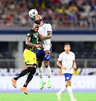 DALLAS, TX - JULY 25: Kellyn Acosta #23 of the United States heads the ball over Junior Flemmings #17 of Jamaica during a game between Jamaica and USMNT at AT&T Stadium on July 25, 2021 in Dallas, Texas.