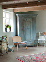 """The large blue-grey cabinet from the 1800s in the bedroom has been paired with  Jonas Lindwall's modern chair """"Papa"""" with a sheepskin cushion"""