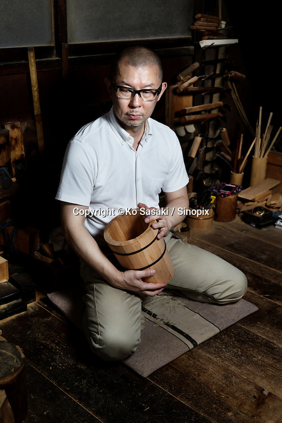Okeei's craftsman Eifu Kawamata with wooden bucket called oke he made