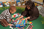 Education preschool 3-4 year olds female teacher sitting on floor working on floor puzzle with boy showing him illustration on box lid as strategy for solving the puzzle horizontal early intervention SEIT