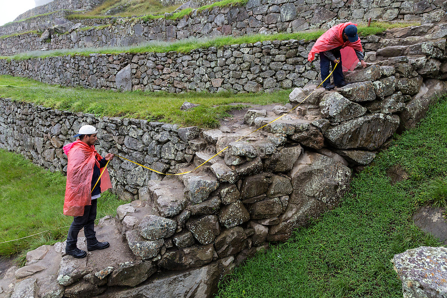Peru, Machu Picchu.  Historic Preservation.  Workers Measuring in Connection with Preservation Work Under Way.