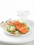 A grilled fillet of salmon served with cucumber salad, on a white plate.