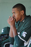 RHP David Garner (16) of the Michigan State Spartans warms his hands in the dugout on a 35-degree day between innings of a game against the Northwestern Wildcats on Sunday, February 17, 2013, at Fluor Field at the West End in Greenville, South Carolina. Garner was named to 2013 Big Ten Players to Watch. Michigan State won, 7-4. (Tom Priddy/Four Seam Images)