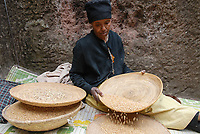 ETHIOPIA, Amhara region, Lalibela , monolith rock churches built by King Lalibela 800 years ago, St. Georg church, orthodox nun baking bread at Bet Giyorgis / AETHIOPIEN Lalibela oder Roha, Koenig LALIBELI liess die monolithischen Felsenkirchen vor ueber 800 Jahren in die Basaltlava auf 2600 Meter Hoehe hauen und baute ein zweites Jerusalem nach, orthodoxe Nonne bereitet Brot an der Georgskirche zu, Bet Giyorgis