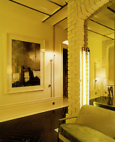 In the living room a neon light creates a warm yellow glow against brick walls painted flat white