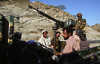Men chewing qat at an army checkpoint on a road in the Abyan region of Yemen. Outside the main towns government control remains weak, restricted to main roads patrolled by the army where vehicles travel in convoy.