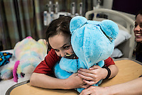 8-year old Beatrice Lipp hugs the Huggable robotic teddy bear in an hospital room at Boston Children's Hospital. Beatrice has been in and out of Hospitals for the last 5 years. Now at Boston Children's Hospital, she is part of a social robotic experiment between Boston's Children Hospital and the Massachusetts Institute of Technology (MIT). The goal of the experiment is to determine whether a so called 'Huggable' teddy bear, a social robotic stereotype, can have therapeutic value for children who have to endure long hospital stays. The bear's talking and movements are remotely controlled by Hospital Staff from outside of the room.