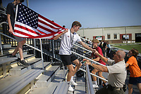 """Eric Pedersen (center) walks steps carrying a flag as he fist bumps Security Officer Ranger Malloy, Thursday, September 9, 2021 at Tiger Stadium in Bentonville. """"What they're doing, we're just emotionally touched,"""" Malloy said of the students, none of whom were born before 9/11. """"They weren't even born and they're out here knocking this out."""" The district is educating students on the 9/11 attacks. Students completed 40 climbs up the home bleachers, the equivalent of the 110 stories (2200 stairs) of the Twin Towers. Check out nwaonline.com/210910Daily/ for today's photo gallery. <br /> (NWA Democrat-Gazette/Charlie Kaijo)"""