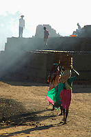 These women carry some 12 bricks each on a small construction site on the road from Mumbai to Goa about 3 hours from Mumbai,India the brick furnace is near by hence the dust and smoke