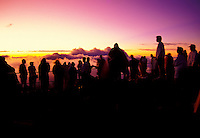 A group of people watch the sun rise at Haleakala National Park at a 9,740-ft. elevation.