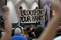 """Protestors stand on the city council desk holding a sign """"Blood on your hand"""" after shutting down the Charlottesville City Council meeting Monday night in Charlottesville, Va. Photo/Andrew Shurtleff"""