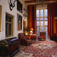 The double-height entrance hall is richly furnished with heavy striped curtains against the window