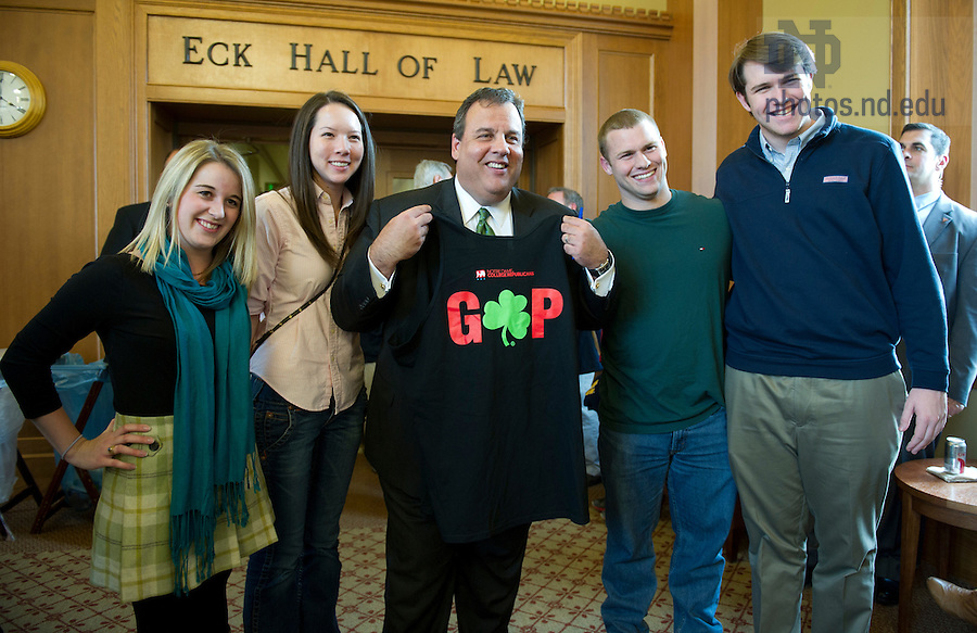 """November 18, 2011; New Jersey Gov. Chris Christie poses for a photo with students as he holds up a T-shirt they gave him during a meet-and-greet in the Eck Commons. Christie delivered the keynote address during a daylong symposium, titled """"Educational Innovation and the Law"""" in the Patrick F. McCartan Courtroom at the Notre Dame Law School. Photo by Barbara Johnston/University of Notre Dame."""