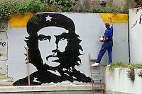 A man begins to paint the colours of the Venezuelan flag onto a Che Guevara mural. Political murals are on walls throughout the city.
