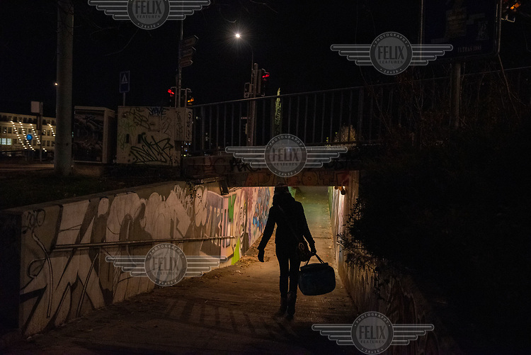 Sylvana Mastromatteo, a volunteer with the homelssness organisation 'le Dream Team', carrying food for the city's homeless, along an exit ramp of a bridge by the Rhone.