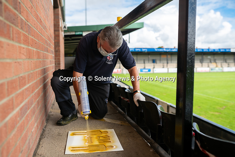 Pictured: Volunteer maintenance worker John Harper sprays a 2 metre stencil in order to comply with social distancing measures during preparations ahead of crowds being welcomed back into sporting events at The Raymond McEnhill Stadium in Salisbury, Wilts.<br /> <br /> Inline with the governments easing of lockdown restrictions, Salisbury Football Club are preparaing to welcome back 30% of their fans as of this Monday, August 31st. <br /> <br /> Salisbury FC play in Southern League Premier Division South, or step 3 of the non-league football ladder. <br /> <br /> © Jordan Pettitt/Solent News & Photo Agency<br /> UK +44 (0) 2380 458800