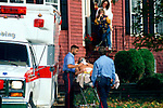 EMTs moving injured man on stretcher out of suburban home toward waiting ambulance as concerned family looks on