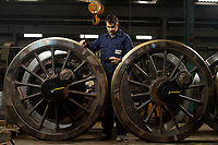 Engineers at the South Devon Railway fitting a new tyre for a steam locomotive.