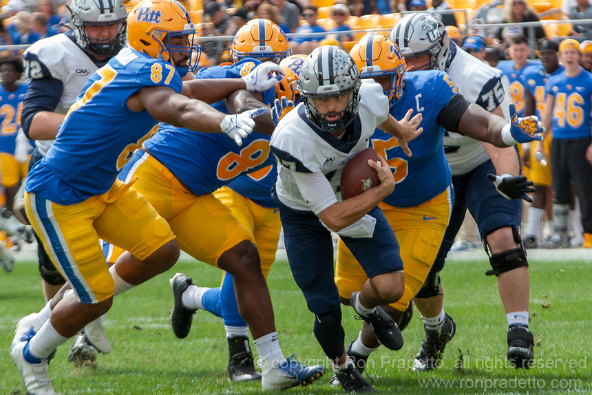 New Hampshire quarterback Bret Edwards (17) tries to escape the pass rush of Pitt defensive lineman Habakkuk Baldonado (87).The Pitt Panthers defeated the New Hampshire Wildcats 77-7 at Heinz Field, Pittsburgh, Pennsylvania on September 25, 2021.