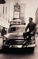 Actor Paul Newman sits on a car and looks at a theater marquee for the play 'Picnic.'. Circa 1956.