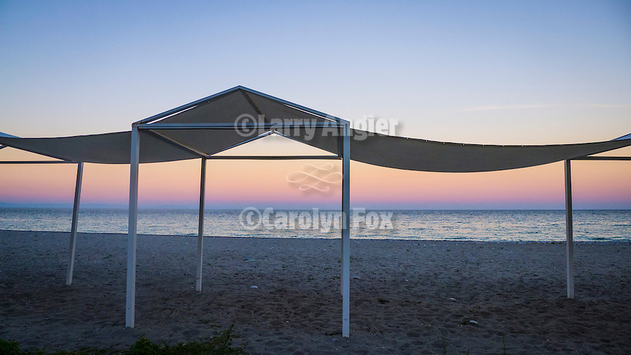 Mare 66 beach resort and sun shelters, on the shore of the Aegean Sea at dusk, Litochoro, Greece