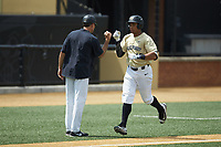Christian Long (19) of the Wake Forest Demon Deacons bumps fists with head coach Tom Walter as he rounds third base after hitting a home run against the Virginia Cavaliers at David F. Couch Ballpark on May 19, 2018 in  Winston-Salem, North Carolina. The Demon Deacons defeated the Cavaliers 18-12. (Brian Westerholt/Four Seam Images)
