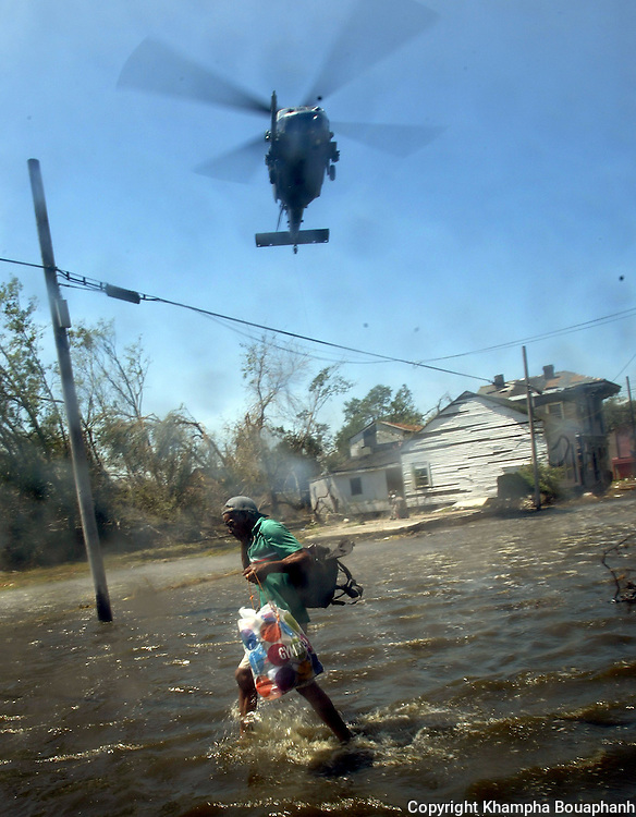A Hurricane Katrina survivor evacuates his home while a rescue copter prepares to pull up another survivor near downtown New Orleans on Wednesday, September 7, 2005.  (photo by Khampha Bouaphanh)