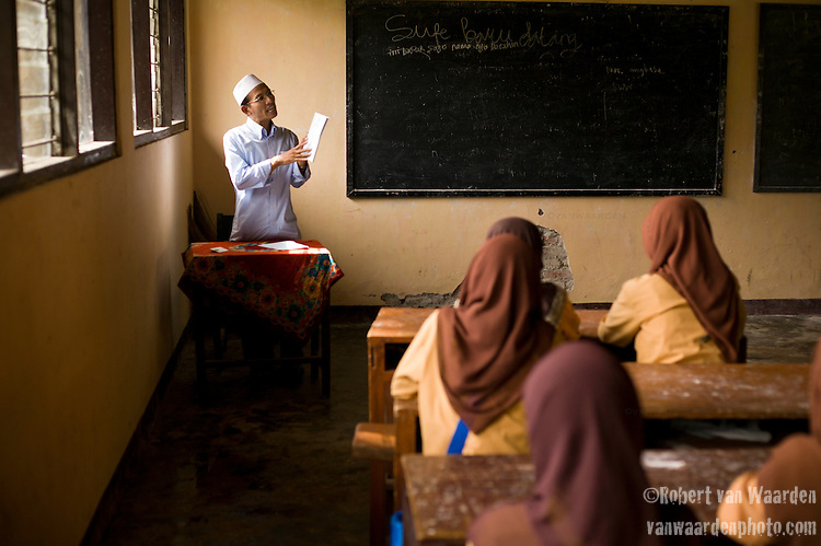 A male teacher at an Islamic boarding school talks to his students. Lombok, Indonesia.