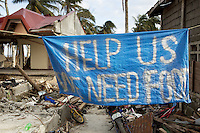 """Philippines. Province Eastern Samar. Hernani. 95 % of the town was destroyed by typhoon Haiyan's winds and storm surge. The population has writen on a banner: """" Help us. We need food."""" Typhoon Haiyan, known as Typhoon Yolanda in the Philippines, was an exceptionally powerful tropical cyclone that devastated the Philippines. Haiyan is also the strongest storm recorded at landfall in terms of wind speed. Typhoon Haiyan's casualties and destructions occured during a powerful storm surge, an offshore rise of water associated with a low pressure weather system. Storm surges are caused primarily by high winds pushing on the ocean's surface. The wind causes the water to pile up higher than the ordinary sea level. 25.11.13 © 2013 Didier Ruef"""
