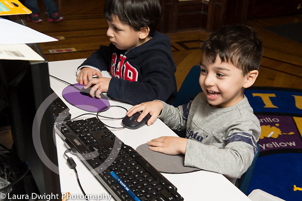 Education Preschool 3 year olds two boys sitting side by side playing on computers