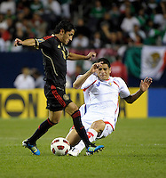 Costa Rica's Jhonny Acosta slide tackles the ball away from Mexico's Angel Reyna.  Mexico defeated Costa Rica 4-1 at the 2011 CONCACAF Gold Cup at Soldier Field in Chicago, IL on June 12, 2011.