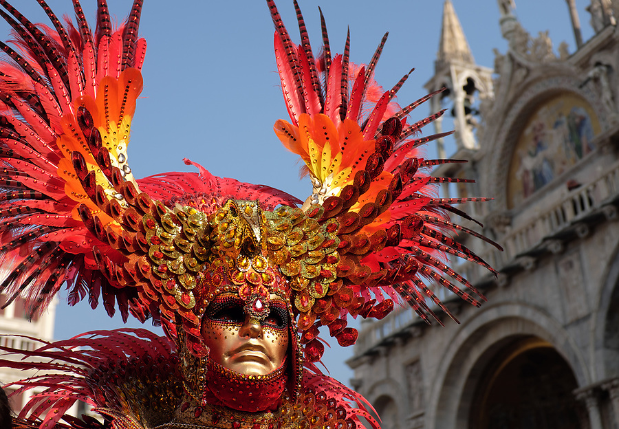 Man dressed in traditional mask and costume for Venice Carnival standing in Piazza San Marco in front of Saint Mark's Basilica, Venice, Veneto, Italy