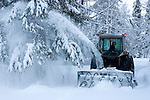 Snowblower removing snow from residence driveway