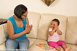 18 month old toddler girl at home with mother clapping with her after finishing puzzle