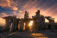 The rising sun beams through a gap in this small tufa formation, complemented by a colorful sky.