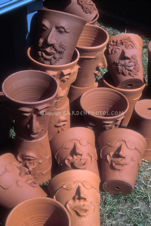 Empty plant pots, with faces, pile of clean cute terracotta gardening pots