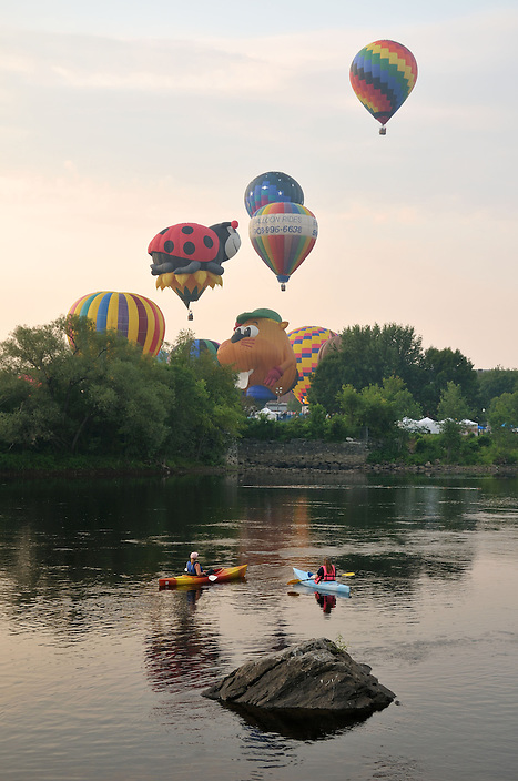 Kayakers taking in the scene from the river at the Lweiston-Auburn Balloon Festival.